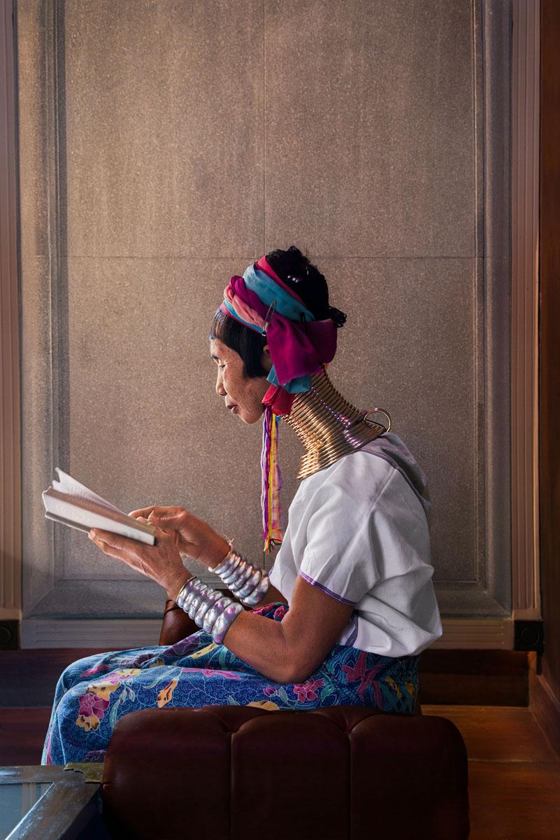 Fotografia di Steve McCurry di una donna tailandese con una grande collana dorata che legge