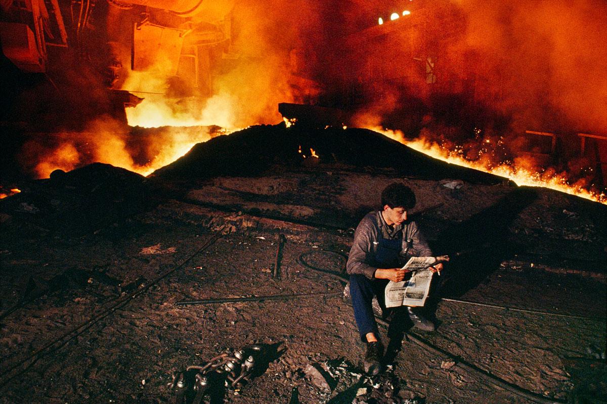 Foto di Steve McCurry di un uomo che legge un giornale in una fabbrica