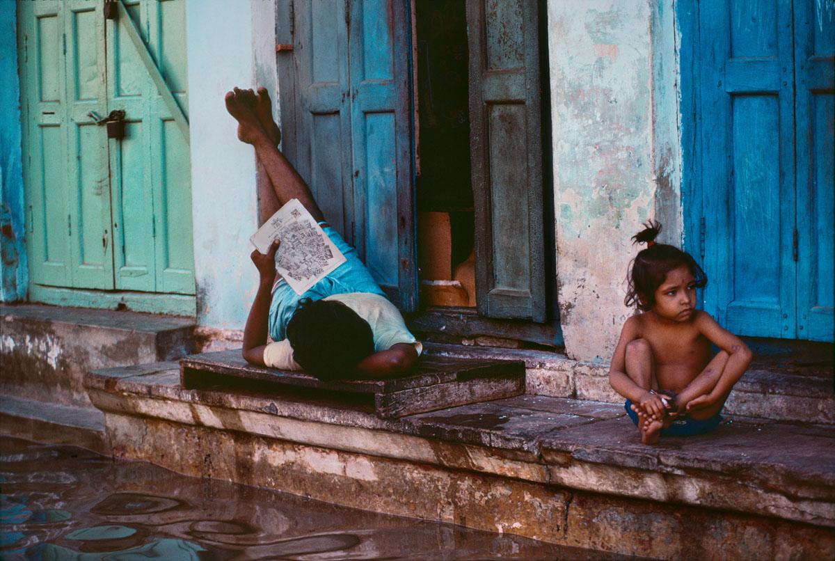 Foto di Steve McCurry di un ragazzo che legge vicino a una strada allagata
