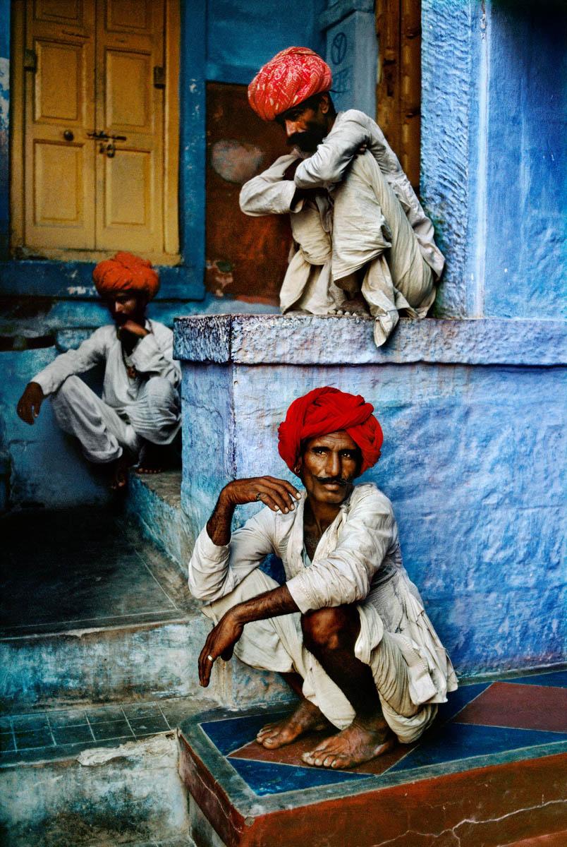 Foto di Steve McCurry di tre uomini seduti nella città blu